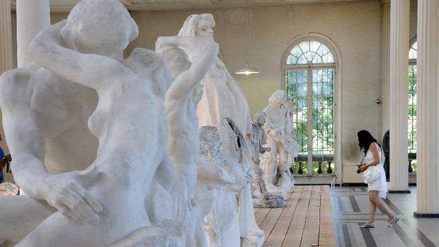 A woman prepares to take a picture, on August 4, 2013, of castings by French sculptor Auguste Rodin (1840-1917) displayed in his studio, close to his house, the