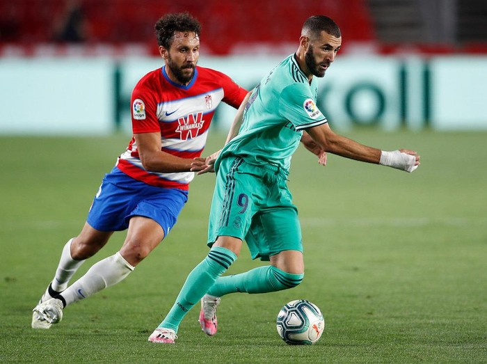 GRANADA, SPAIN - JULY 13:  Karim Benzema of Real Madrid is tackled by Germán Sánchez of Granada during the Liga match between Granada CF and Real Madrid CF at on July 13, 2020 in Granada, Spain. Football Stadiums around Europe remain empty due to the Coronavirus Pandemic as Government social distancing laws prohibit fans inside venues resulting in all fixtures being played behind closed doors. (Photo by Fran Santiago/Getty Images)