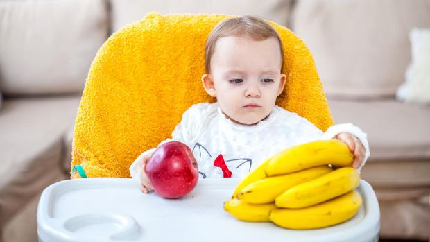Little baby girl sitting in baby chair eating fruit apple and bananas