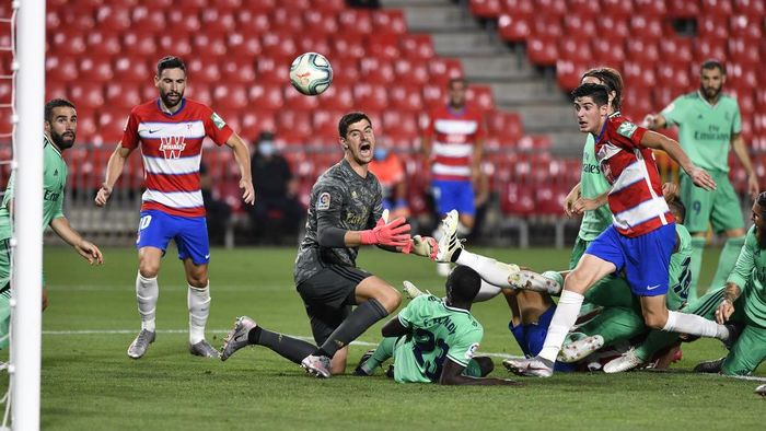 Granadas Spanish forward Carlos Fernandez (R) challenges Real Madrids Belgian goalkeeper Thibaut Courtois (L) and French defender Ferland Mendy (down) during the Spanish league football match Granada FC vs Real Madrid CF at Nuevo Los Carmenes stadium in Granada on July 13, 2020. (Photo by JORGE GUERRERO / AFP)