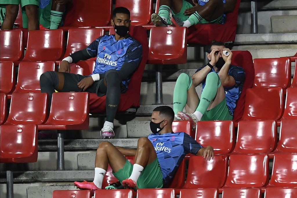 Real Madrid's Gareth Bale, right, gestures from the stands ahead of the Spanish La Liga soccer match between Granada and Real Madrid at the Los Carmenes stadium in Granada, Spain, Monday, July 13, 2020. (AP Photo/Jose Breton)