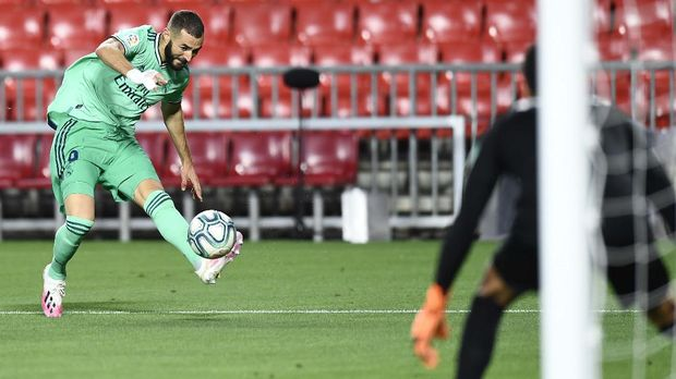 Real Madrid's Karim Benzema kicks the ball during the Spanish La Liga soccer match between Granada and Real Madrid at the Los Carmenes stadium in Granada, Spain, Monday, July 13, 2020. (AP Photo/Jose Breton)