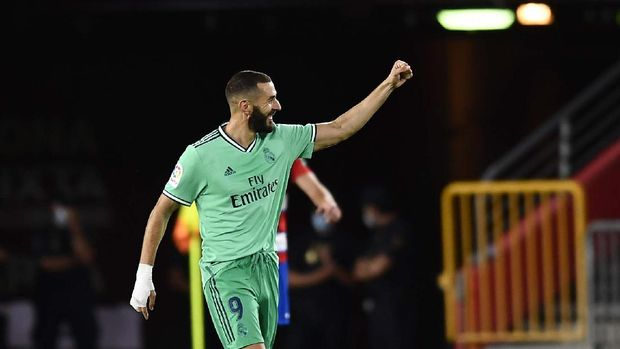 Real Madrid's Karim Benzema celebrates after scoring his side's second goal during the Spanish La Liga soccer match between Granada and Real Madrid at the Los Carmenes stadium in Granada, Spain, Monday, July 13, 2020. (AP Photo/Jose Breton)