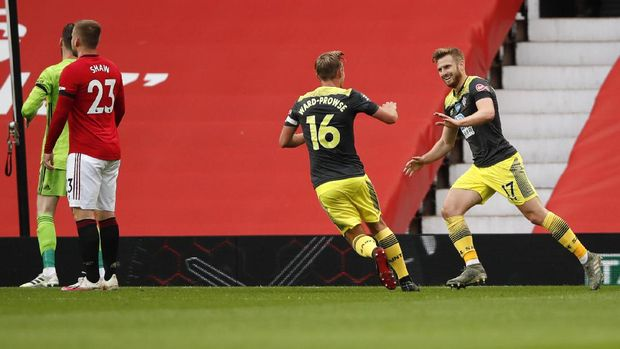 Southampton's Stuart Armstrong, right, is congratulated by teammate James Ward-Prowse after scoring his team's first goal during the English Premier League soccer match between Manchester United and Southampton at Old Trafford in Manchester, England, Monday, July 13, 2020. (AP Photo/Peter Powell,Pool)