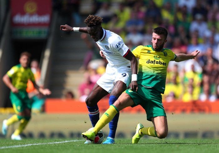 NORWICH, ENGLAND - AUGUST 24: Grant Hanley of Norwich City battles for possession with Tammy Abraham of Chelsea during the Premier League match between Norwich City and Chelsea FC at Carrow Road on August 24, 2019 in Norwich, United Kingdom. (Photo by Catherine Ivill/Getty Images)