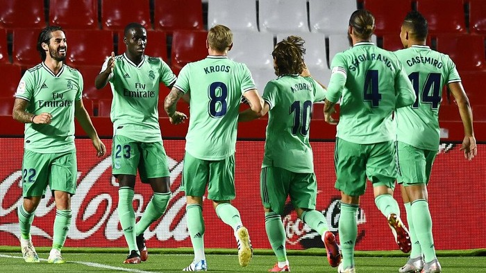 Real Madrids Ferland Mendy, second left, celebrates after scoring with teammates the opening goal during the Spanish La Liga soccer match between Granada and Real Madrid at the Los Carmenes stadium in Granada, Spain, Monday, July 13, 2020. (AP Photo/Jose Breton)