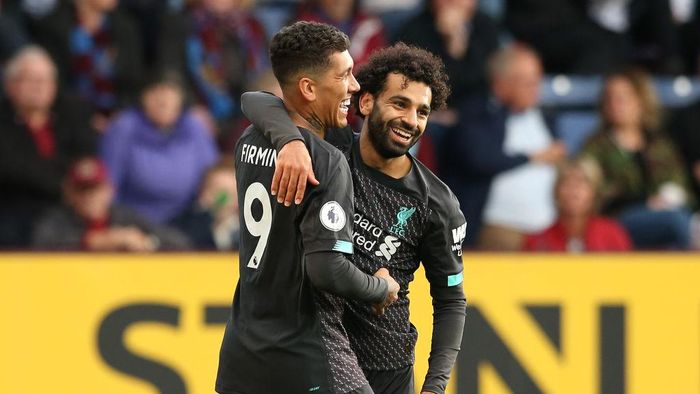 BURNLEY, ENGLAND - AUGUST 31: Roberto Firmino of Liverpool celebrates with teammate Mohamed Salah after scoring his teams third goal  during the Premier League match between Burnley FC and Liverpool FC at Turf Moor on August 31, 2019 in Burnley, United Kingdom. (Photo by Jan Kruger/Getty Images)
