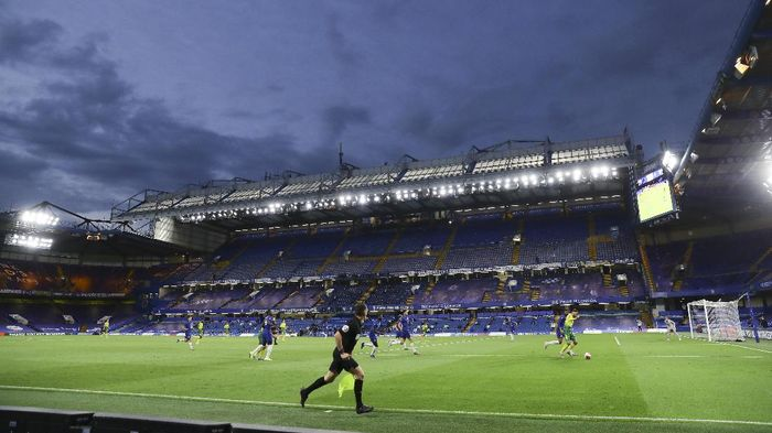 A groundsman sprays disinfectant on the goal posts during a break in the English Premier League soccer match between Chelsea and Norwich City at Stamford Bridge in London, England, Tuesday, July 14, 2020. (AP Photo/Julian Finney,Pool)