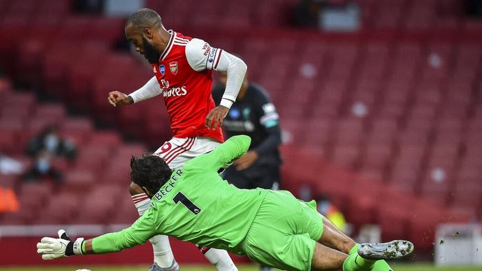 Arsenals Alexandre Lacazette runs past Liverpools goalkeeper Alisson before scoring his team first goal during the English Premier League soccer match between Arsenal and Liverpool at the Emirates Stadium in London, England, Wednesday, July 15, 2020. (Glyn Kirk/Pool via AP)
