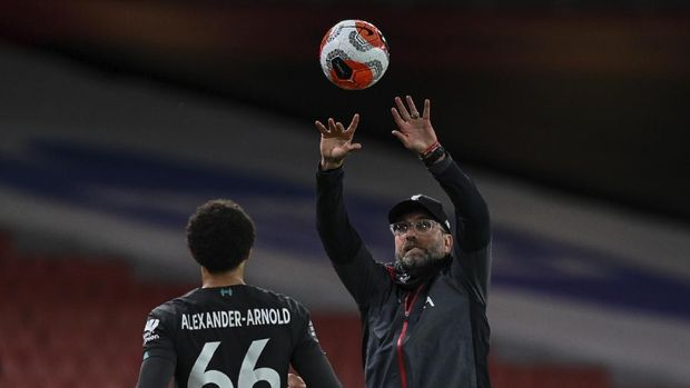Liverpool's manager Jurgen Klopp passes the ball to Liverpool's Trent Alexander-Arnold during the English Premier League soccer match between Arsenal and Liverpool at the Emirates Stadium in London, England, Wednesday, July 15, 2020. (Shaun Botterill/Pool via AP)