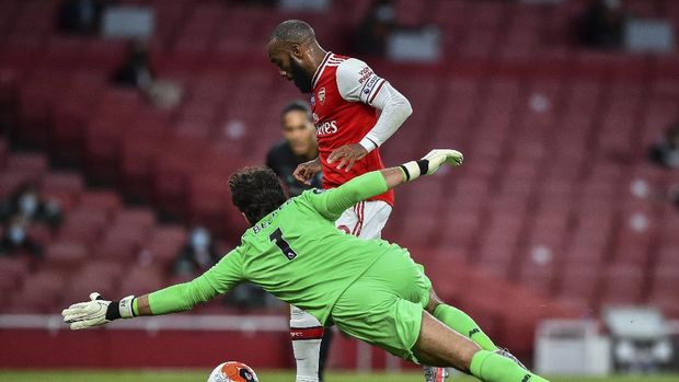 Arsenal's Alexandre Lacazette runs past Liverpool's goalkeeper Alisson before scoring his team first goal during the English Premier League soccer match between Arsenal and Liverpool at the Emirates Stadium in London, England, Wednesday, July 15, 2020. (Glyn Kirk/Pool via AP)