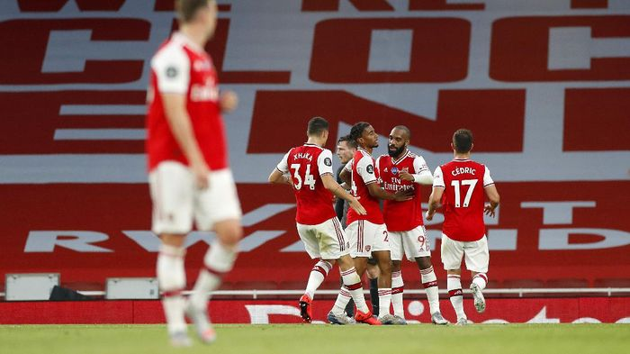 LONDON, ENGLAND - JULY 15: Reiss Nelson of Arsenal celebrates with teammates after scoring his sides second goal during the Premier League match between Arsenal FC and Liverpool FC at Emirates Stadium on July 15, 2020 in London, England. Football Stadiums around Europe remain empty due to the Coronavirus Pandemic as Government social distancing laws prohibit fans inside venues resulting in all fixtures being played behind closed doors. (Photo by Paul Childs/Pool via Getty Images)