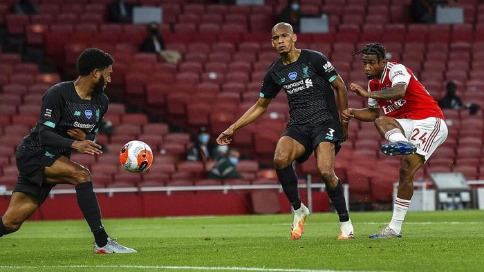 Arsenals Reiss Nelson, right, scores his team second goal during the English Premier League soccer match between Arsenal and Liverpool at the Emirates Stadium in London, England, Wednesday, July 15, 2020. (Glyn Kirk/Pool via AP)