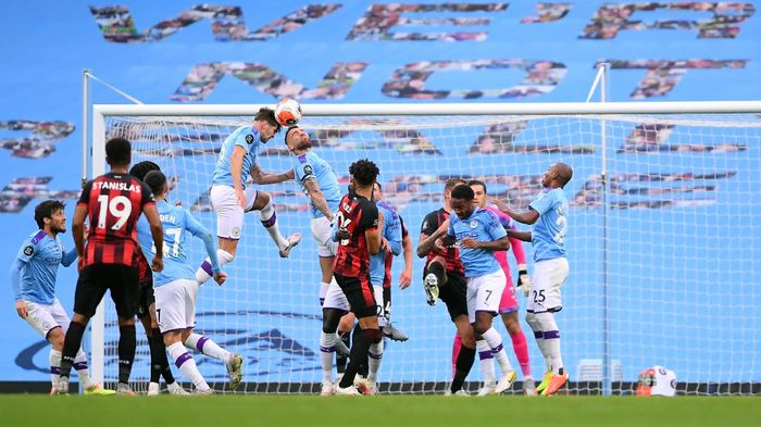 MANCHESTER, ENGLAND - JULY 15: John Stones and Nicolas Otamendi of Manchester City jump for the ball during the Premier League match between Manchester City and AFC Bournemouth  at Etihad Stadium on July 15, 2020 in Manchester, England. Football Stadiums around Europe remain empty due to the Coronavirus Pandemic as Government social distancing laws prohibit fans inside venues resulting in all fixtures being played behind closed doors. (Photo by Laurence Griffiths/Getty Images)