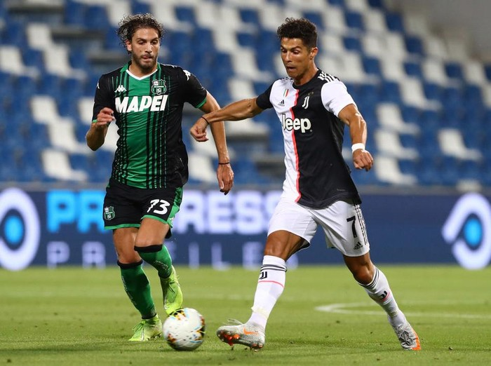 REGGIO NELLEMILIA, ITALY - JULY 15:  Cristiano Ronaldo (R) of Juventus FC is challenged by Manuel Locatelli (L) of US Sassuolo during the Serie A match between US Sassuolo and Juventus at Mapei Stadium - Citta del Tricolore on July 15, 2020 in Reggio nellEmilia, Italy.  (Photo by Marco Luzzani/Getty Images)