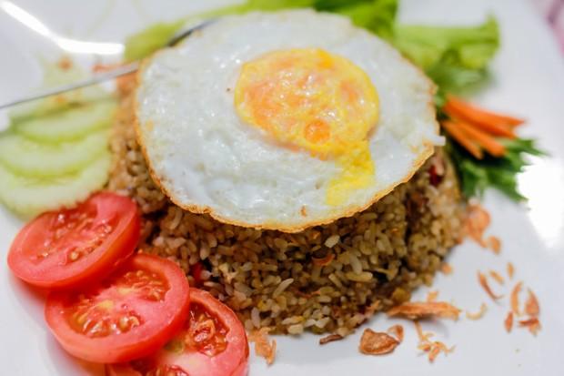 Nasi goreng dengan nasi yang pera berbumbu pedas meresap yang lengkap dengan acar timun dan kerupuk memang tidak ada duanya.