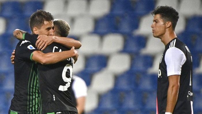 Sassuolos Filip Djuricic, left, celebrates with Francesco Caputo after scoring a goal during a Serie A soccer match between Sassuolo and Juventus at the Mapei Stadium in Reggio Emilia, Italy, Wednesday, July 15, 2020. (Massimo Paolone/LaPresse via AP)