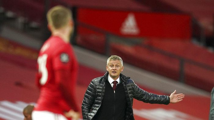 Manchester Uniteds manager Ole Gunnar Solskjaer gestures as he talks to Manchester Uniteds Luke Shaw during the English Premier League soccer match between Manchester United and Southampton at Old Trafford in Manchester, England, Monday, July 13, 2020. (AP Photo/Dave Thompson,Pool)