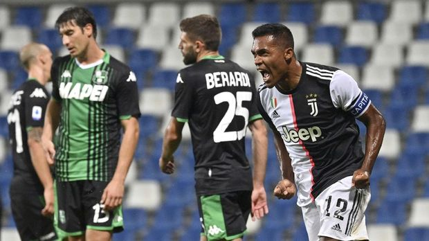 Juventus' Alex Sandro, right, celebrates after scoring a goal during a Serie A soccer match between Sassuolo and Juventus at the Mapei Stadium in Reggio Emilia, Italy, Wednesday, July 15, 2020. (Massimo Paolone/LaPresse via AP)