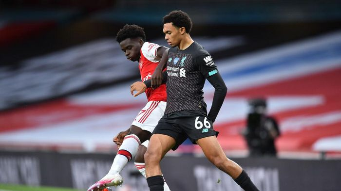 LONDON, ENGLAND - JULY 15: Bukayo Saka of Arsenal  battles for possession with  Trent Alexander-Arnold of Liverpool  during the Premier League match between Arsenal FC and Liverpool FC at Emirates Stadium on July 15, 2020 in London, England. Football Stadiums around Europe remain empty due to the Coronavirus Pandemic as Government social distancing laws prohibit fans inside venues resulting in all fixtures being played behind closed doors. (Photo by Glyn Kirk/Pool via Getty Images)
