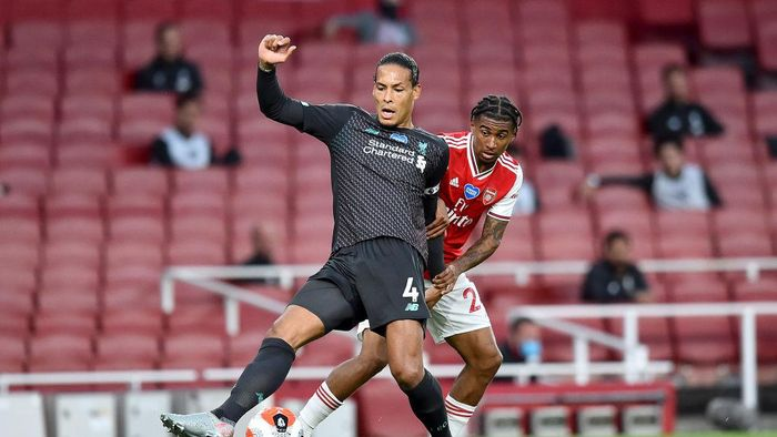 LONDON, ENGLAND - JULY 15: Virgil van Dijk of Liverpool is challenged by Reiss Nelson of Arsenal during the Premier League match between Arsenal FC and Liverpool FC at Emirates Stadium on July 15, 2020 in London, England. Football Stadiums around Europe remain empty due to the Coronavirus Pandemic as Government social distancing laws prohibit fans inside venues resulting in all fixtures being played behind closed doors. (Photo by Glyn Kirk/Pool via Getty Images)