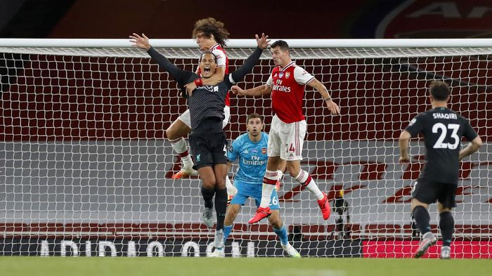 LONDON, ENGLAND - JULY 15: Virgil van Dijk of Liverpool jumps for the ball with David Luiz of Arsenal during the Premier League match between Arsenal FC and Liverpool FC at Emirates Stadium on July 15, 2020 in London, England. Football Stadiums around Europe remain empty due to the Coronavirus Pandemic as Government social distancing laws prohibit fans inside venues resulting in all fixtures being played behind closed doors. (Photo by Paul Childs/Pool via Getty Images)