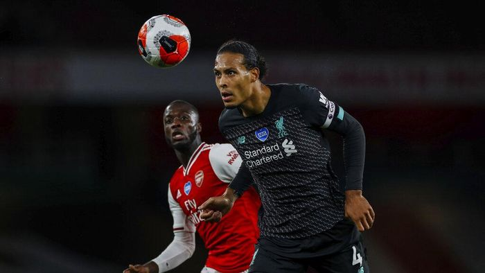 Liverpools Virgil van Dijk, right, duels for the ball with Arsenals Nicolas Pepe during the English Premier League soccer match between Arsenal and Liverpool at the Emirates Stadium in London, England, Wednesday, July 15, 2020. (Paul Childs/Pool via AP)