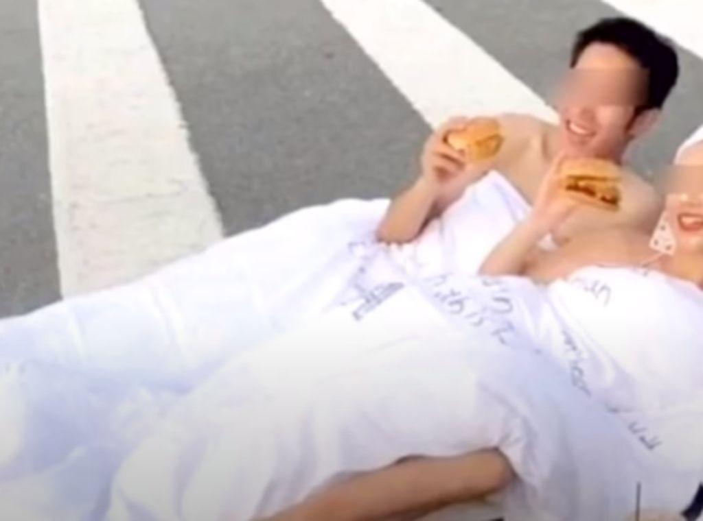 Foto Tiduran di Tengah Jalan Sambil Makan Burger, Pasangan Ini Dikecam Netizen