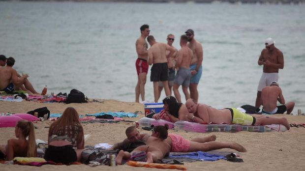 Tourists enjoy the beach at the Spanish Balearic island of Mallorca, Spain, Thursday, July 16, 2020. In a move designed to stop the spread of the new coronavirus and shake off the region's reputation as a party hub, regional authorities in the Balearic Islands ordered the closure from Thursday of all establishments along Mallorca's