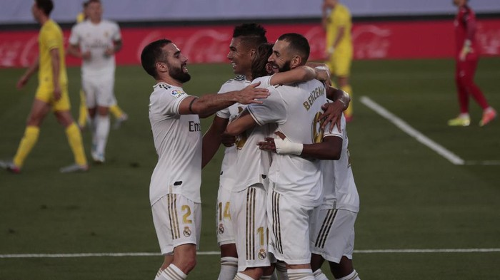 Real Madrids Karim Benzema, right, celebrates with his teammates after scoring during the Spanish La Liga soccer match between Real Madrid and Villareal at the Alfredo di Stefano stadium in Madrid, Spain, Thursday, July 16, 2020. (AP Photo/Bernat Armangue)