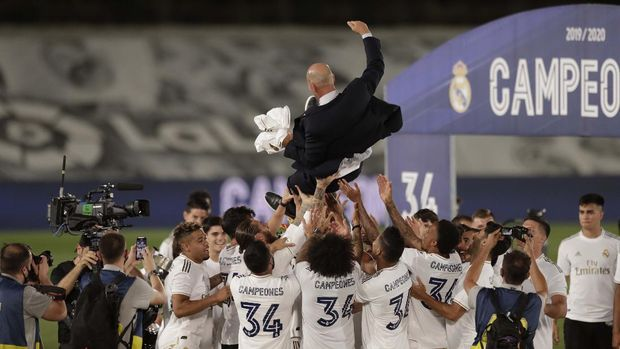 Real Madrid's head coach Zinedine Zidane, holds the trophy as he poses for the photographers after winning the Spanish La Liga 2019-2020 following a soccer match between Real Madrid and Villareal at the Alfredo di Stefano stadium in Madrid, Spain, Thursday, July 16, 2020. (AP Photo/Bernat Armangue)