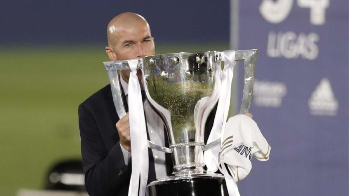 Real Madrids head coach Zinedine Zidane, holds the trophy as he poses for the photographers after winning the Spanish La Liga 2019-2020 following a soccer match between Real Madrid and Villareal at the Alfredo di Stefano stadium in Madrid, Spain, Thursday, July 16, 2020. (AP Photo/Bernat Armangue)
