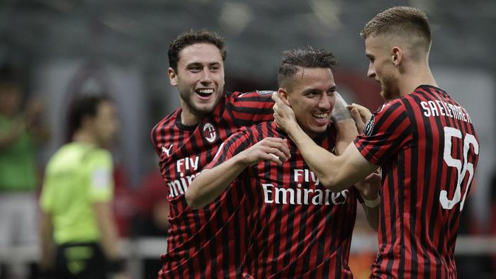 AC Milans Ismael Bennacer, centre, celebrates with team players after scoring during a Serie A soccer match between AC Milan and Bologna, at the San Siro stadium in Milan, Italy, Saturday, July 18, 2020. (AP Photo/Luca Bruno)