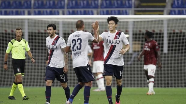 Bologna's Takehiro Tomiyasu of Japan, centre, celebrates after scoring during a Serie A soccer match between AC Milan and Bologna, at the San Siro stadium in Milan, Italy, Saturday, July 18, 2020. (AP Photo/Luca Bruno)
