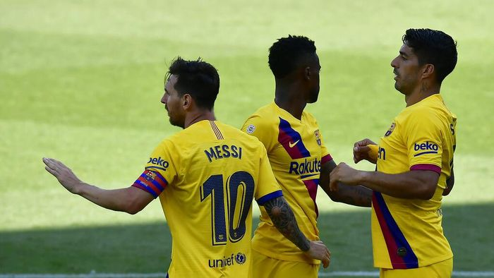 Barcelonas Nelson Semedo, center, celebrates with his teammates Lionel Messi, left, and Luis Suarez, his goal against Alaves during the Spanish La Liga soccer match between Alaves and FC Barcelona, at Mendizorroza stadium, in Vitoria, northern Spain, Sunday, July 19, 2020. (AP Photo/Alvaro Barrientos)