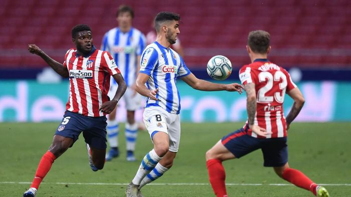 MADRID, SPAIN - JULY 19: Mikel Merino of Real Sociedad is challenged by Thomas Partey and Kieran Trippier of Atletico during the Liga match between Club Atletico de Madrid and Real Sociedad at Wanda Metropolitano on July 19, 2020 in Madrid, Spain. (Photo by Denis Doyle/Getty Images)