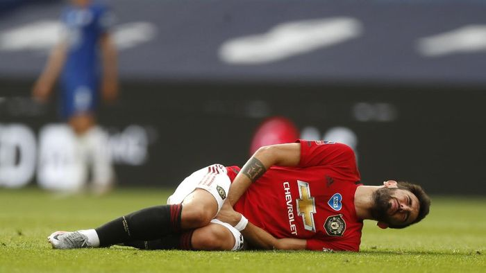 Manchester Uniteds Bruno Fernandes grimaces after getting injured during the English FA Cup semifinal soccer match between Chelsea and Manchester United at Wembley Stadium in London, England, Sunday, July 19, 2020. (AP Photo/Alastair Grant, Pool)