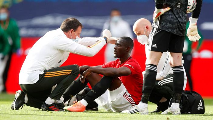 LONDON, ENGLAND - JULY 19: Eric Bailly of Manchester United is seen to by medical staff after a collision during the FA Cup Semi Final match between Manchester United and Chelsea at Wembley Stadium on July 19, 2020 in London, England. Football Stadiums around Europe remain empty due to the Coronavirus Pandemic as Government social distancing laws prohibit fans inside venues resulting in all fixtures being played behind closed doors. (Photo by Alastair Grant/Pool via Getty Images)