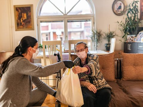 Female volunteer bringing groceries to a senior woman at home