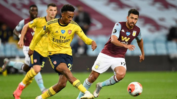 BIRMINGHAM, ENGLAND - JULY 21: Joe Willock of Arsenal shoots past Trezeguet of Aston Villa  during the Premier League match between Aston Villa and Arsenal FC at Villa Park on July 21, 2020 in Birmingham, England. Football Stadiums around Europe remain empty due to the Coronavirus Pandemic as Government social distancing laws prohibit fans inside venues resulting in all fixtures being played behind closed doors. (Photo by Peter Powell/Pool via Getty Images)
