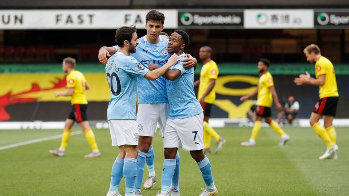 WATFORD, ENGLAND - JULY 21: Raheem Sterling of Manchester City celebrates with his team after he scores his teams first goal during the Premier League match between Watford FC and Manchester City at Vicarage Road on July 21, 2020 in Watford, England. Football Stadiums around Europe remain empty due to the Coronavirus Pandemic as Government social distancing laws prohibit fans inside venues resulting in all fixtures being played behind closed doors. (Photo by Adrian Dennis/Pool via Getty Images)
