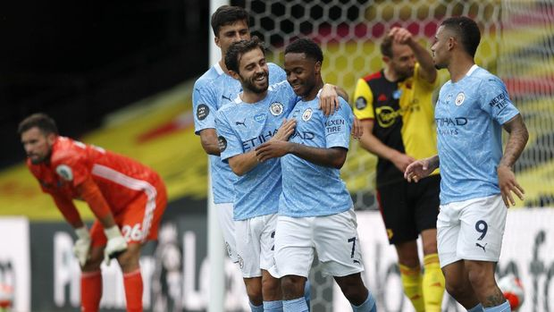 Manchester City's Raheem Sterling, centre, celebrates with teammates after scoring his side's second goal during the English Premier League soccer match between Watford and Manchester City at the Vicarage Road Stadium in Watford, England, Tuesday, July 21, 2020. (Adrian Dennis/Pool via AP)
