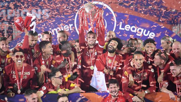 Liverpool's Jordan Henderson lifts the English Premier League trophy following the English Premier League soccer match between Liverpool and Chelsea at Anfield Stadium in Liverpool, England, Wednesday, July 22, 2020. Liverpool are champions of the EPL for the season 2019-2020. The trophy is presented at the teams last home game of the season. Liverpool won the match against Chelsea 5-3. (Laurence Griffiths, Pool via AP)