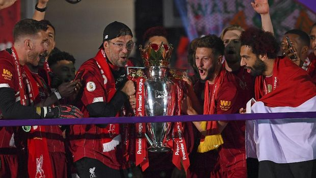 Liverpool's manager Jurgen Klopp and Liverpool's Adam Lallana hold the English Premier League trophy following the English Premier League soccer match between Liverpool and Chelsea at Anfield Stadium in Liverpool, England, Wednesday, July 22, 2020. Liverpool are champions of the EPL for the season 2019-2020. The trophy is presented at the teams last home game of the season. Liverpool won the match against Chelsea 5-3. (Laurence Griffiths, Pool via AP)
