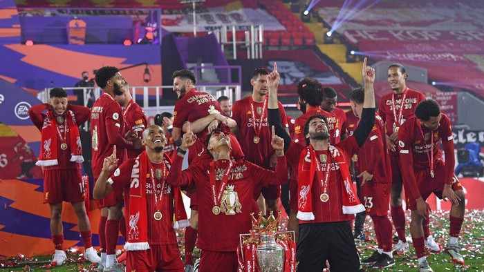 Liverpools Fabinho, left, Liverpools goalkeeper Alisson, right, and Roberto Firmino, all from Brazil, celebrate with the English Premier League trophy following the English Premier League soccer match between Liverpool and Chelsea at Anfield Stadium in Liverpool, England, Wednesday, July 22, 2020. Liverpool are champions of the EPL for the season 2019-2020. The trophy is presented at the teams last home game of the season. Liverpool won the match against Chelsea 5-3. (Laurence Griffiths, Pool via AP)