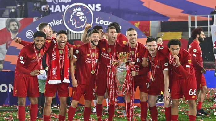 Liverpool players celebrate with the English Premier League trophy after it was presented following the Premier League soccer match between Liverpool and Chelsea at Anfield stadium in Liverpool, England, Wednesday, July 22, 2020. (Paul Ellis, Pool via AP)