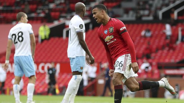 Manchester United's Mason Greenwood celebrates after scoring his side's opening goal during the English Premier League soccer match between Manchester United and West Ham at the Old Trafford stadium in Manchester, England, Wednesday, July 22, 2020. (Cath Ivill/Pool via AP)