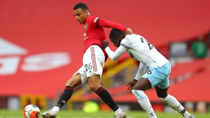 MANCHESTER, ENGLAND - JULY 22: Mason Greenwood of Manchester United and Arthur Masuaku of West Ham United battle for the ball during the Premier League match between Manchester United and West Ham United at Old Trafford on July 22, 2020 in Manchester, England. Football Stadiums around Europe remain empty due to the Coronavirus Pandemic as Government social distancing laws prohibit fans inside venues resulting in all fixtures being played behind closed doors. (Photo by Catherine Ivill/Getty Images)