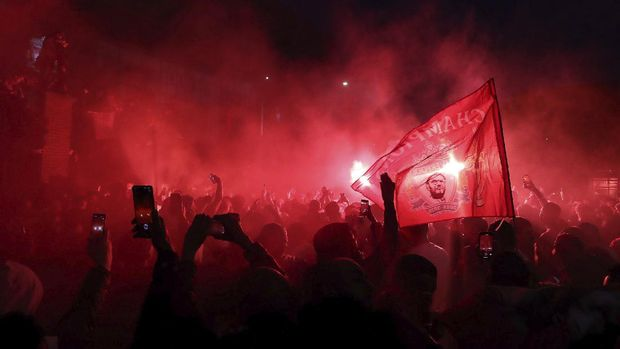 Liverpool fans celebrate outside Anfield stadium after the English Premier soccer match between Liverpool and Chelsea, Wednesday, July 22, 2020, in Liverpool, England. (Martin Rickett/PA via AP)