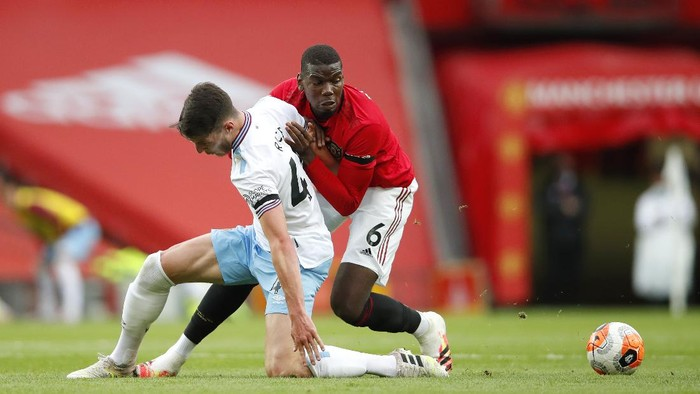 MANCHESTER, ENGLAND - JULY 22: Paul Pogba of Manchester United and Declan Rice of West Ham United battle for the ball during the Premier League match between Manchester United and West Ham United at Old Trafford on July 22, 2020 in Manchester, England. Football Stadiums around Europe remain empty due to the Coronavirus Pandemic as Government social distancing laws prohibit fans inside venues resulting in all fixtures being played behind closed doors. (Photo by Clive Brunskill/Getty Images)